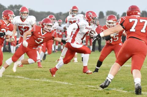 Norfolk Catholic running back Dylan Kautz splits through the Trojan defenders