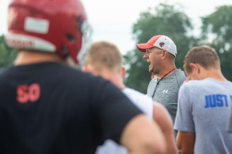 Cedar Catholic's football coach Chad Cattau meets with his team during the first practice of the season. Photo by Elsie Stormberg
