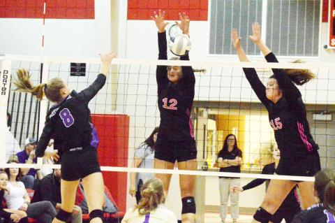 Cedar Catholic's Maddie Wieseler goes up for a block during Mid-States Conference action last week against Battle creek. Cedar earned a four-set win to stay unbeaten in the conference.