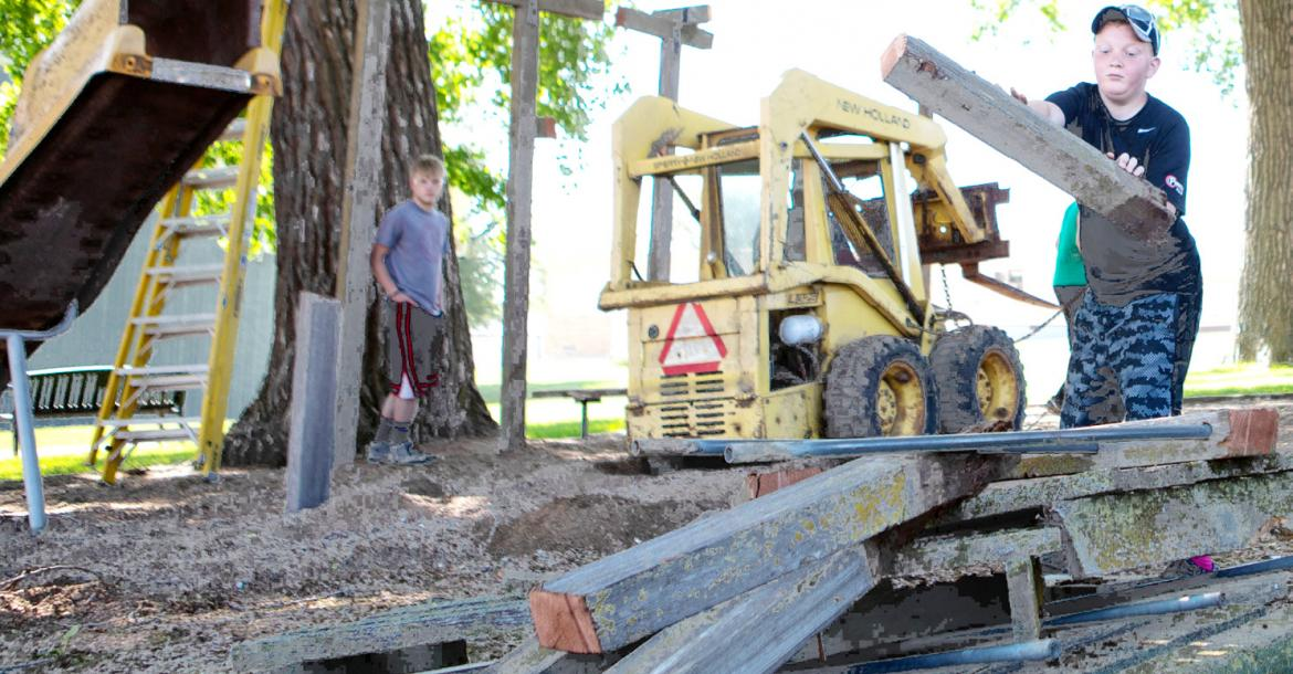Aric Hall tosses an old post torn out of the ground during the Tractor Park destruction in Coleridge, Wednesday, May 30