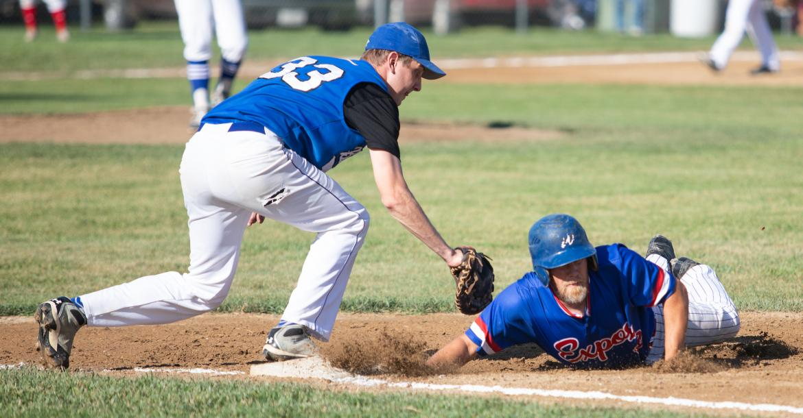 Wynot Expos's Don Whitmire slides back into first base during a game against Crofton at the districts tournament in Lesterville. Photo by Elsie Stormberg