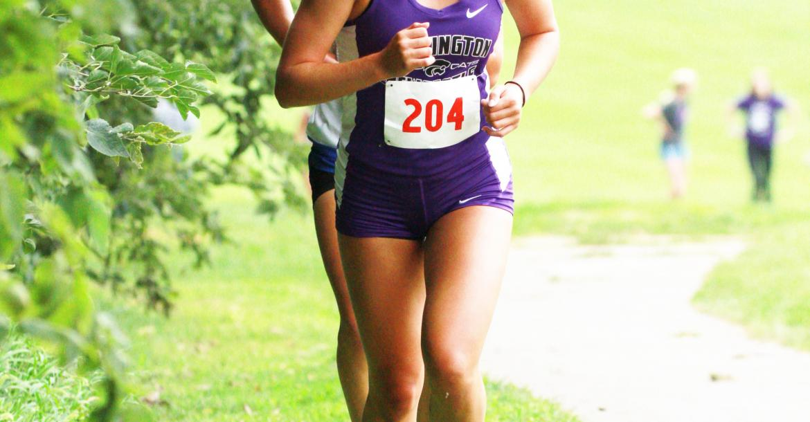 Hartington-Newcastle's Jayda Bernecker fights to keep pace ahead of another runner as she runs up a hill.