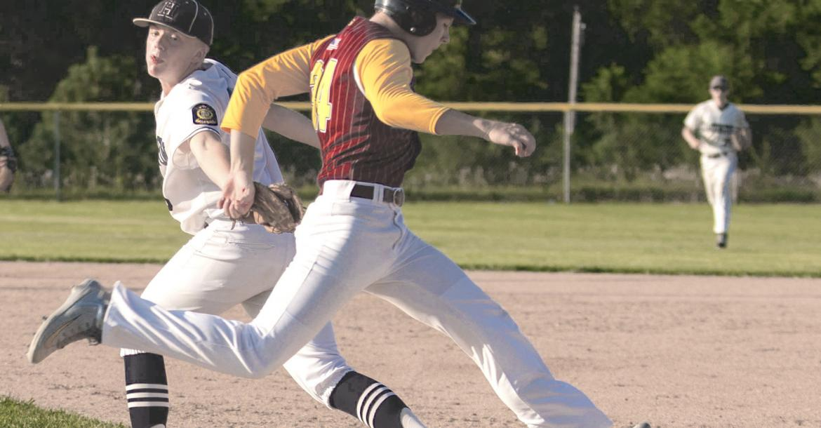 Hartington's Ted Bengston attempts to tag out Neligh's Dawson Kaup during a game at the Class C District tournament in Pierce on Monday