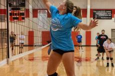 Cedar Catholic's Abby Hochstein tips the ball over the net during a drill. Photo by Elsie Stormberg