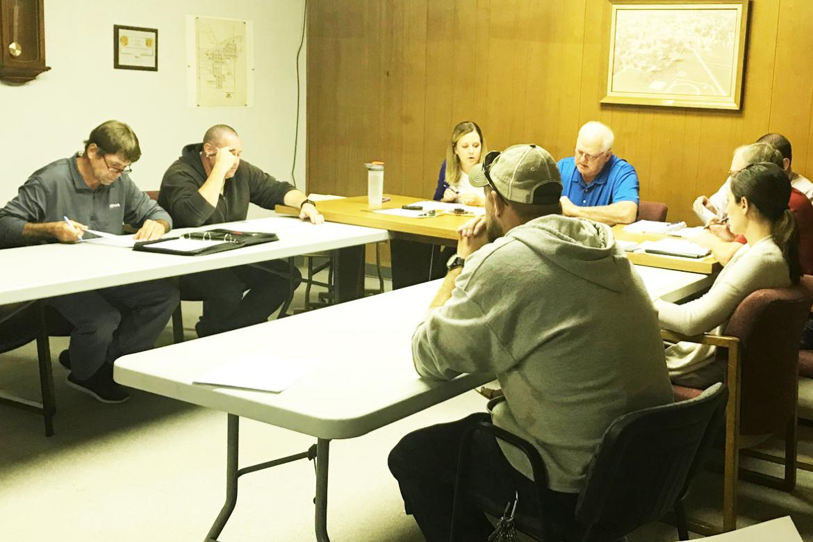 City Council members, along with City Administrator Kelsey Backer and Mayor Dwayne Schutt, look over information during Wednesday's Council meeting. The meeting drew quite a large crowd as local residents came out to share their views on a proposed new medical clinic